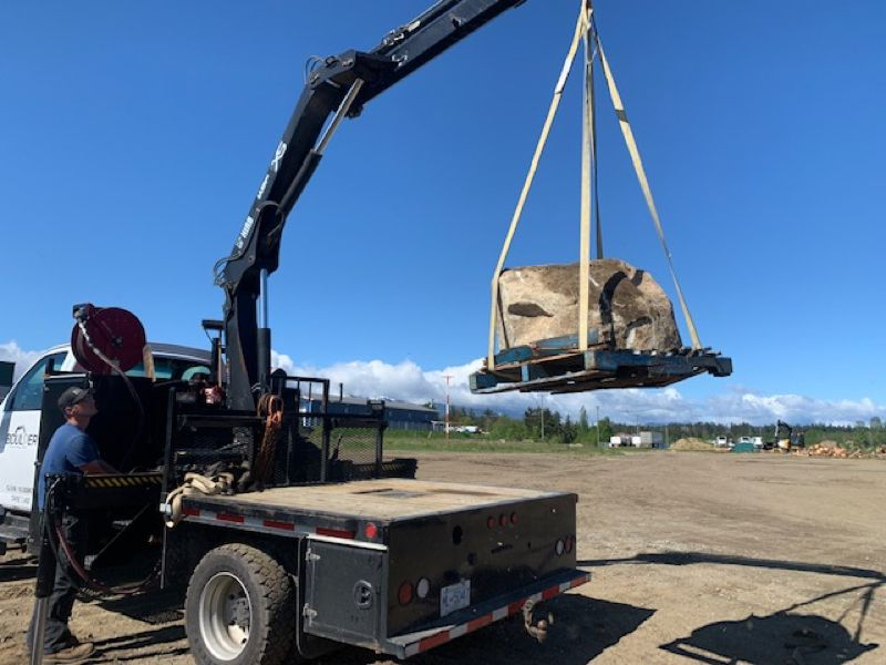 lifting large rock with truck